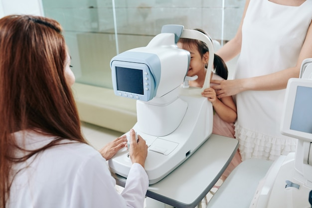 Pediatric ophthalmologist using refractometer eye test machine when checking eyesight of little girl