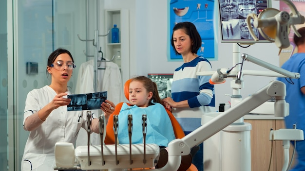 Pediatric woman dentist treating little girl patient in modern stomatological dentistry office showing teeth x-ray explaining to mother dental intervention. visiting dentist with children.