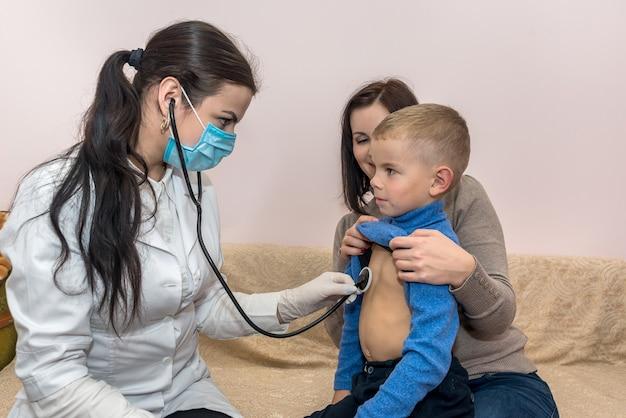 방문 시 작은 환자의 심장 박동을 확인하는 소아과 의사