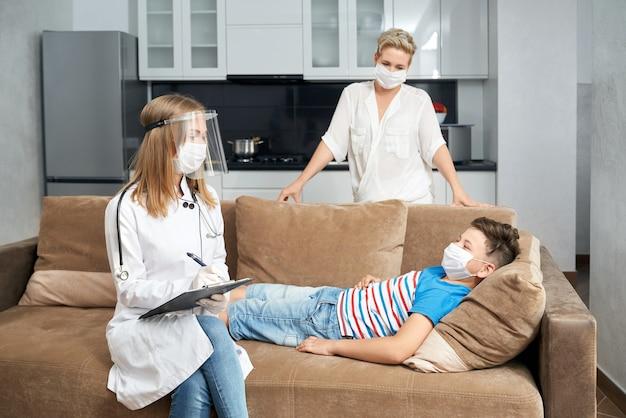 유행성 동안 집에서 아픈 소년을 검사하는 소아과 의사 프리미엄 사진