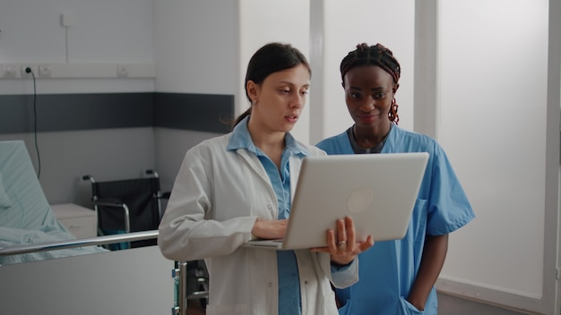 소아과 의사는 아프리카인에게 노트북에 대한 의료 전문 지식을 보여주는 아동 질병 회복에 대해 논의합니다.