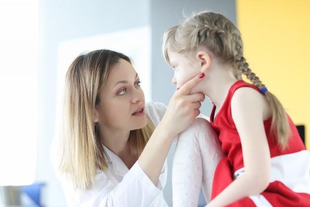 小児科医は子供の概念の扁桃炎の小さな女の子の喉の治療を調べます