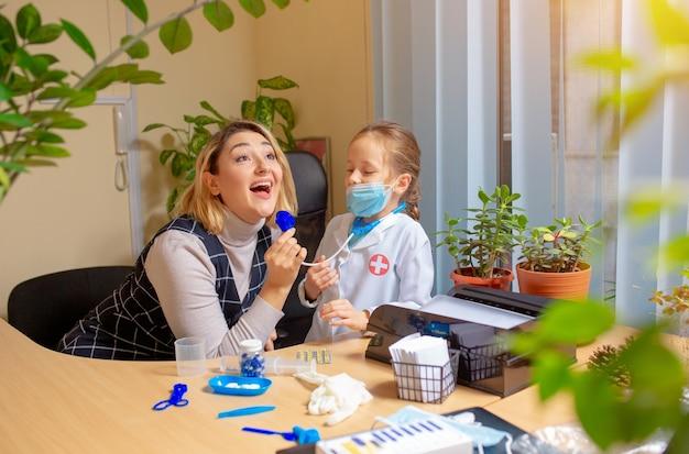 Врач педиатр осматривает ребенка в удобном медицинском кабинете. здравоохранение, детство, медицина, концепция защиты и профилактики.