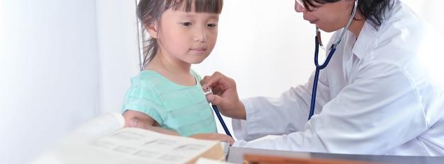 小児科医の医師が聴診器の広いバナーの背景で小さな女の子の肺を聞きます。