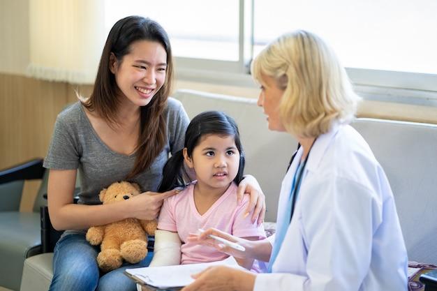 병원에서 깁스를 하고 팔이 부러진 작은 아시아 소녀를 검사하는 소아과 의사