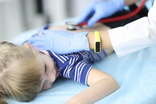 고무 장갑에 소아과 의사는 어린이의 폐를 경청