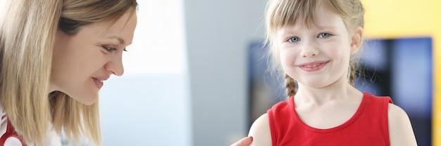 小児科医の医師は、子供の概念の肩の予防接種で少女に接種します