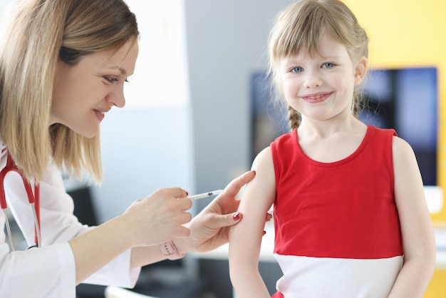 Врач педиатр делает прививку маленькой девочке в плечо