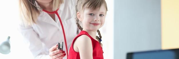 소아과 의사는 청진기와 소녀의 폐를 수신합니다. 숨가쁨 개념 진단하기