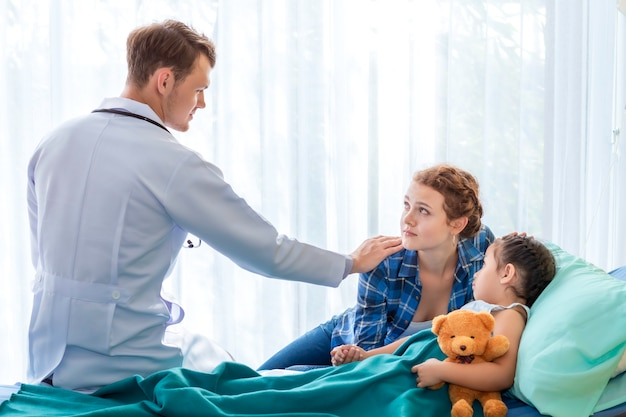 Pediatrician (doctor) reassuring and discussing patient girl and her mother on bedroom hospital.