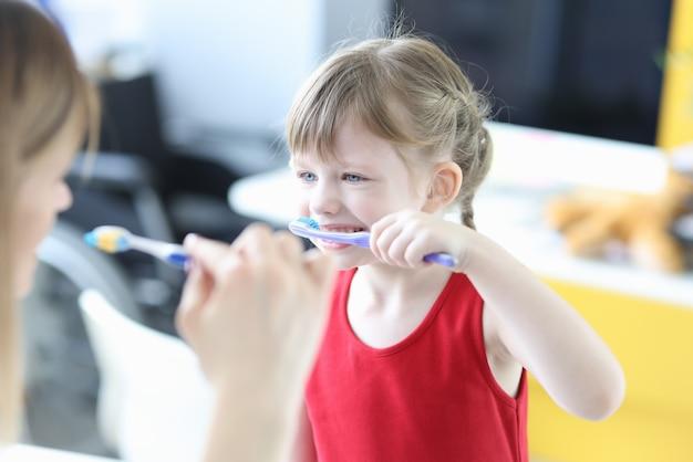 小さな女の子に歯を磨くように教える小児科医