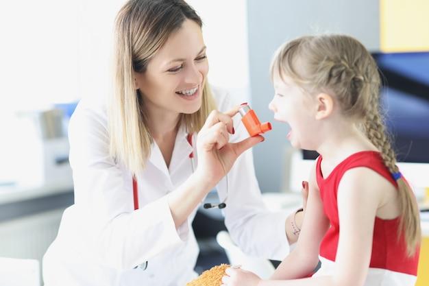 Врач-педиатр учит маленькую девочку использовать гормональный ингалятор в клинике лечения