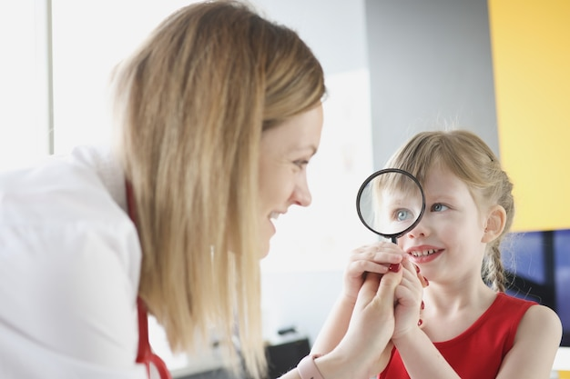 Pediatrician doctor with little girl holding magnifying glass finding right treatment for child