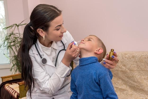 小児科医がクリニックの小さな男の子に鼻を垂らしている