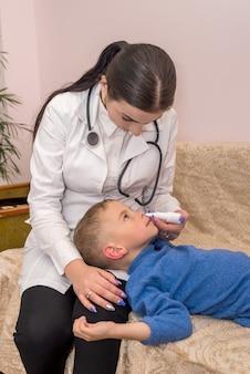小児科医がクリニックで小さな患者に鼻を落とす