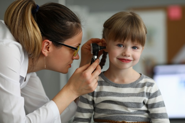 Pediatrician examines ear of sick child in office