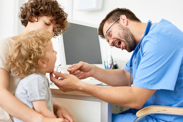 小児科医が小さな男の子を調べる