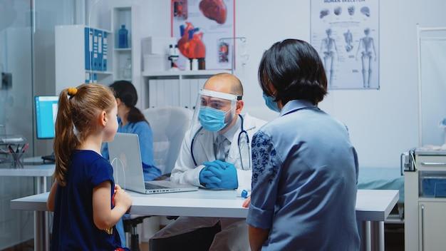保護マスクを着用した少女に治療を説明する小児科医。 covid-19の間に医療サービス、相談、病院での治療を提供する保護マスクを備えた医学の専門家
