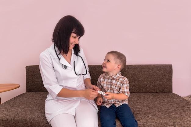 소아과 의사는 작은 환자에게 물집에 약을 제공합니다