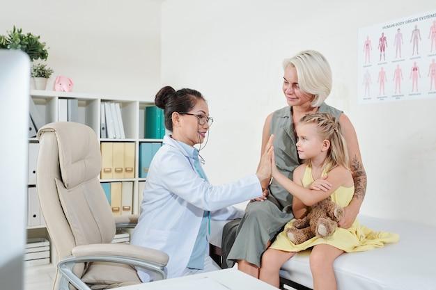 彼の小さな患者にハイタッチを与える小児科医