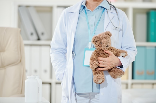 Педиатр держит плюшевого мишку