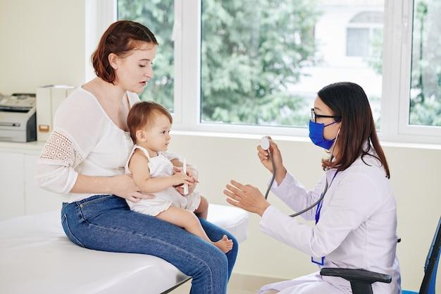 彼女の母親の膝の上に座っている愛らしい少女の心拍をチェックする医療マスクの小児科医