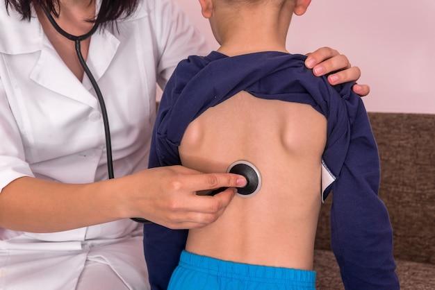 聴診器を背負って少年の呼吸を聞いている小児科医