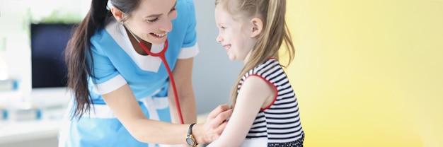 クリニックで少女の肺と心臓を聞いている小児科医