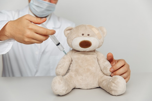 Pediatrician makes an injection for teddy bear. child healtcare and treatment concept.