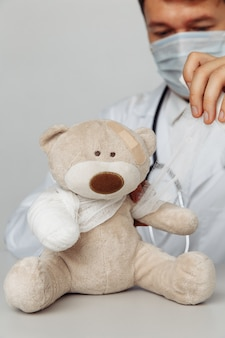 Pediatrician in mask bandage teddy bear in medical office closeup