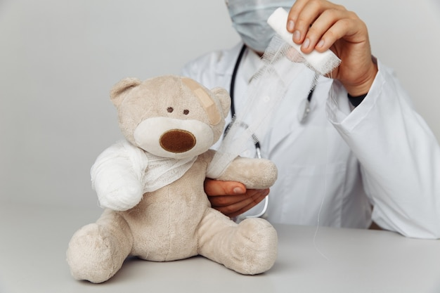 Pediatrician in mask bandage teddy bear in medical office