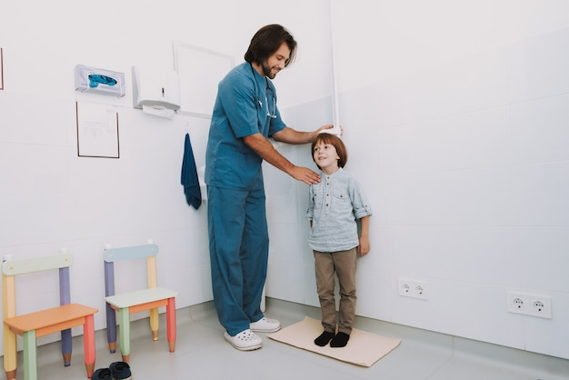 Pediatrician measures kids height regular checkup.