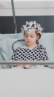 Врач-педиатр женщина-врач обсуждает экспертизу эволюции болезни при мониторинге томографии мозга во время консультации по выздоровлению. больной ребенок в гарнитуре с датчиками мозга eeg в больничной палате