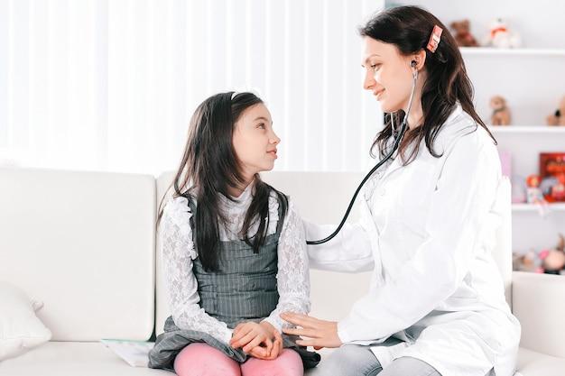 小児科医は少女に治療のルールを積極的に説明します。