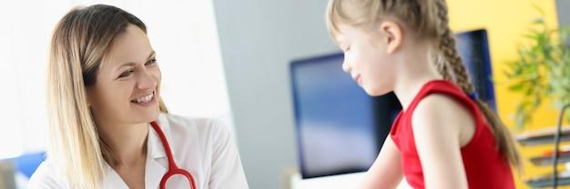 소아과 의사는 어린 소녀에게 어린이를 위한 과일의 접시 혜택에 다른 과일을 보여줍니다