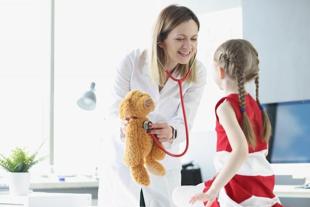 소아과 의사는 어린 소녀에게 장난감을 사용하여 청진기를 사용하는 방법을 보여줍니다.