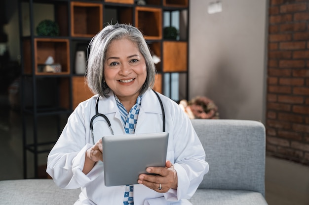 Pediatrician smile while using tablet