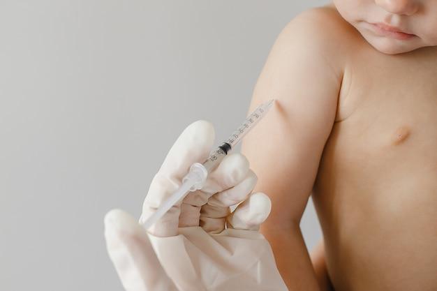 小児科クリニックで小さな子供に予防接種をする小児科医
