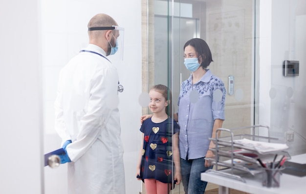 Pediatrician wearing face mask against coronavirus during consultation of child. physician, specialist in medicine with protection mask providing health services, consultation.