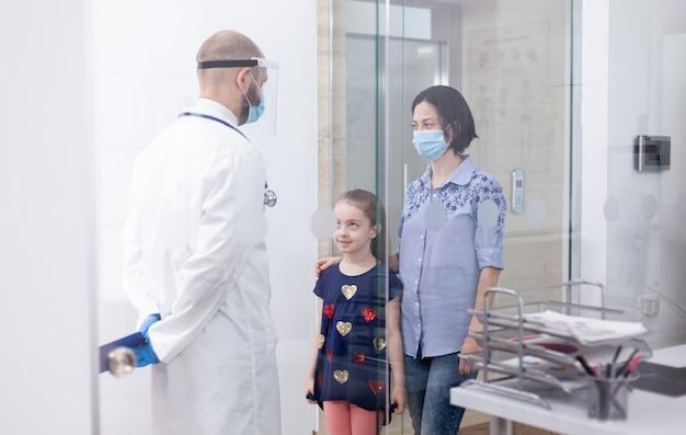 소아과 의사는 아이와 상담하는 동안 코로나바이러스에 대한 얼굴 마스크를 착용합니다. 의사, 의료 서비스, 상담을 제공하는 보호 마스크가 있는 의학 전문가.