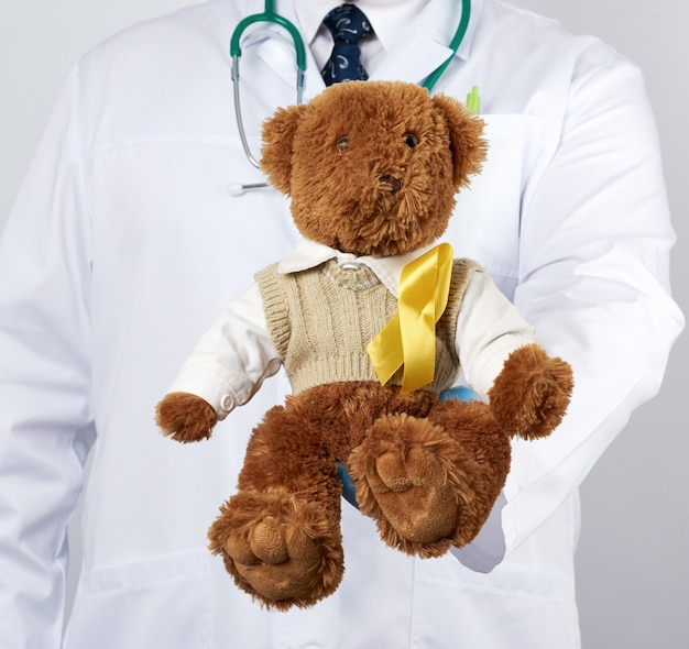 Pediatrician in white coat, blue latex gloves holds a brown teddy bear with a yellow ribbon on a sweater, concept of the fight against childhood cancer