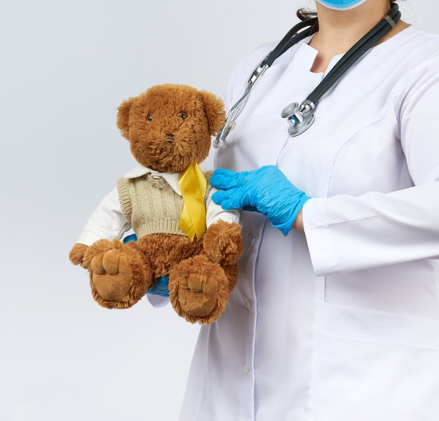 Pediatrician in white coat, blue latex gloves holds a brown teddy bear with a yellow ribbon on a sweater