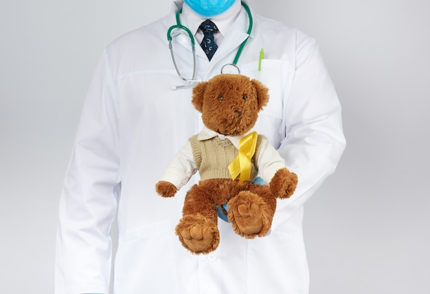 Pediatrician in white coat, blue latex gloves holds a brown teddy bear