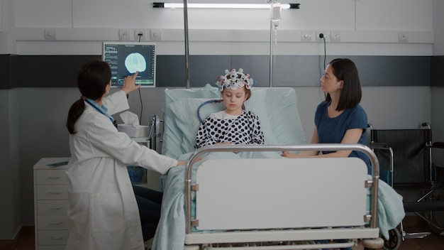 回復相談中に病気の進展を監視しながら断層撮影の専門知識について話し合う小児科医の女性医師。病棟で脳波センサーヘッドセットを装着した病気の子供