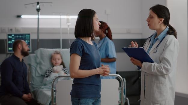 黒人看護師が病気の症状を監視しながら、心配している母親に回復治療を説明する小児科医の女性医師。病気の呼吸手術後に回復しているベッドで休んでいる病気の子供