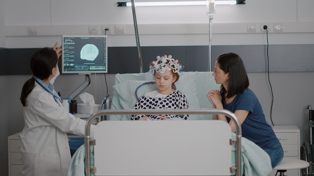 脳断層撮影の専門知識を分析しながら病気の進展を監視する小児科医の女性医師
