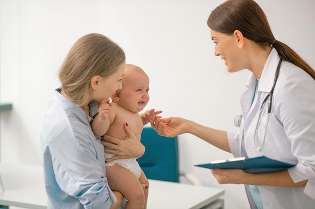 小児科医。彼女の小さな赤ちゃんと一緒に小児科医を訪問している若いお母さん