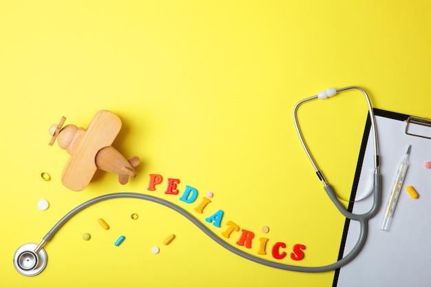 小児科の概念聴診器と明るい背景のおもちゃ