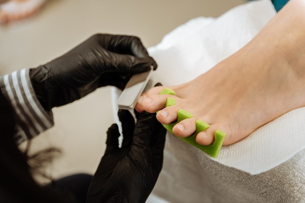 Pedicure for client. experienced professional chiropodist making black gloves making pedicure for her client