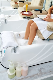 Pedicure feet bath in sofa chair at nails salon